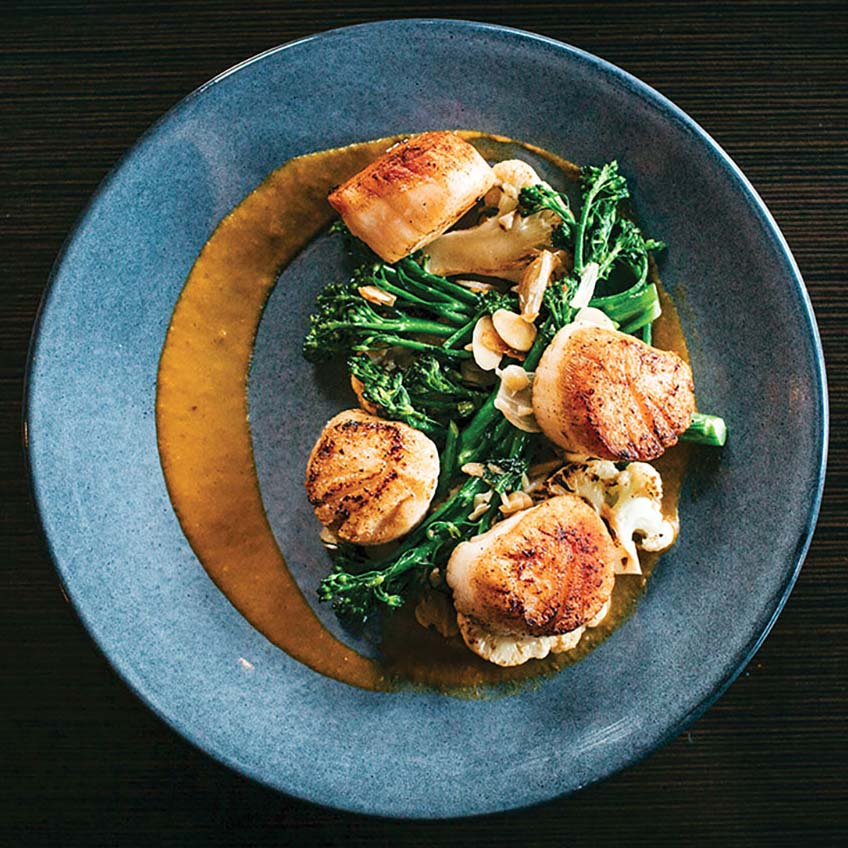An elegant scallop dish with cooked greens and sauce at the Heritage, a fine dining restaurant in Richmond, VA