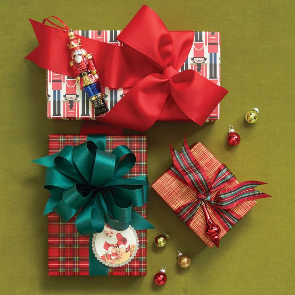 One present is wrapped in a graphic Nutcracker print, with a wide red bow and a Nutcracker ornament. A another is wrapped in a tradition red and green plaid with a deep green bow and a vintage-looking Santa Tag. The third is wrapped in red paper with crisscrossed gold times, plaid ribbon, and a red ornament