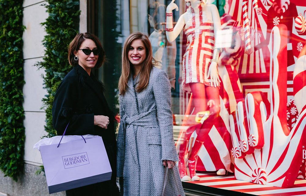 Alison Bruhn and Delia Folk stand outside Bergdorf Goodman in New York with a shopping bag.