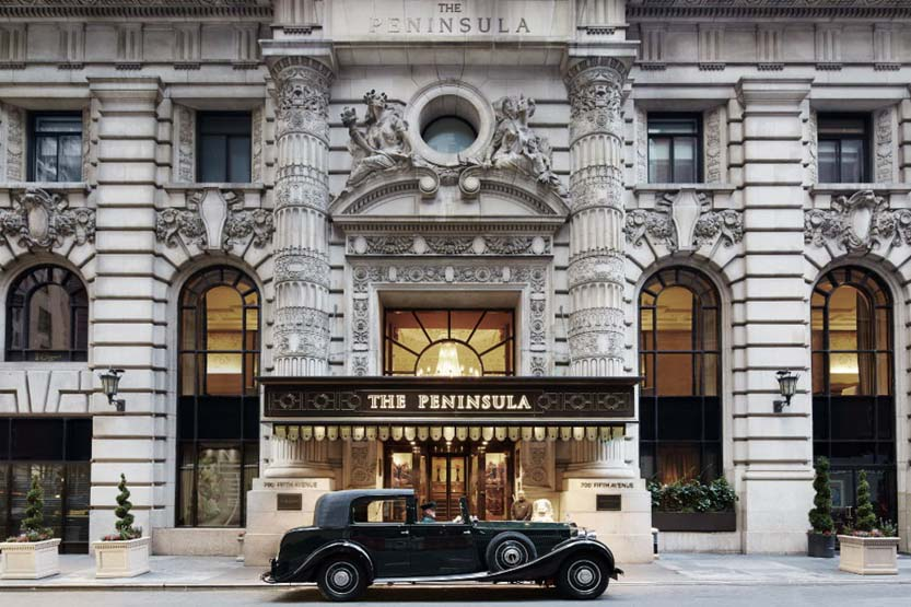 Vew of Peninsula Hotel New York's ornate facade, with a class Rolls Royce parked in front