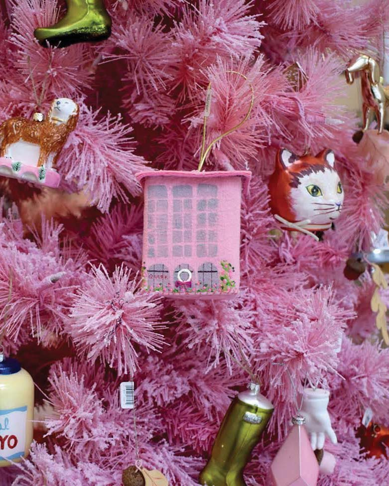 Close-up of ornaments on a pink Christmas trees, including a small building ornament by Heather Donohue and vintage-looking blown glass ornaments depicting a holiday stocking, a cat, and a dog, among others.