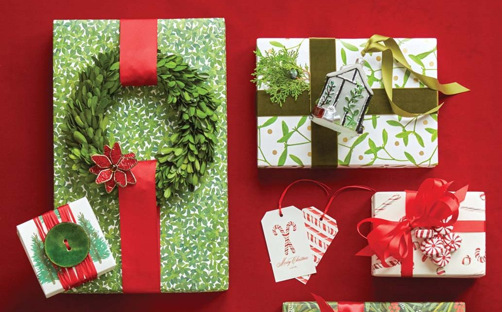 Red and green holiday gift wrap ideas. Adornments attached to ribbons include a large green button, a small green wreath, faux peppermint candies, a blown glass tree ornament, and a greenery sprig.