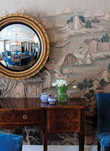 Photo of a convex gold-framed circular mirror above a sideboard, in dining room papered in Gracie's 'Ming Village.' Blue-and-white pottery pieces and a vase of white tulips sit on the sideboard