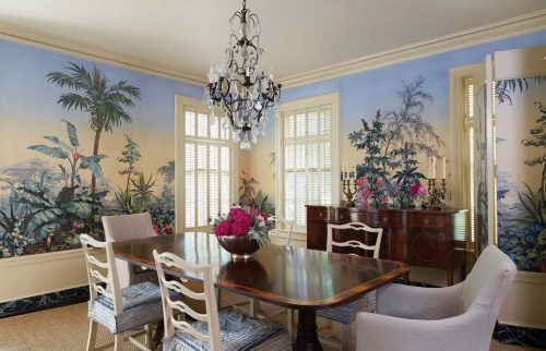 Dining room with a crystal chandelier and antique table and sideboard, surrounded by scenic wallpaper panels