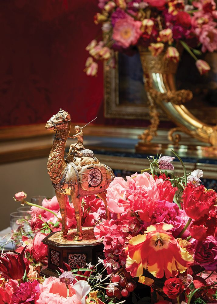 The lush floral arrangement features a range of pink and coral flowers, with touches of yellow, around a gilded sculpture of a woman riding a camel
