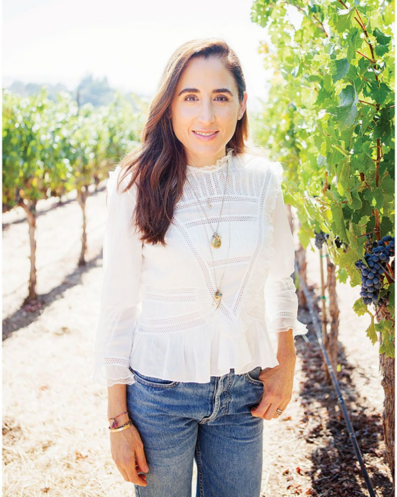 April Gargiulo stands in a vineyard wearing a white 3/4-sleeve top and jeans