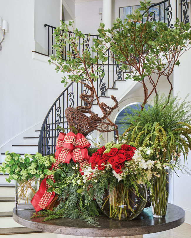 A grand Christmas floral display files a circular table. In the background, a staircase with black iron railing curves around the wall of the rotunda.