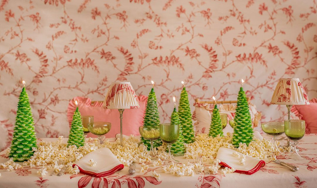 Christmas tree-shaped candles adorn a table dressed in a soft red and white botanical tablecloth print, napkins, and small lamp. Popcorn decorates the table, too.