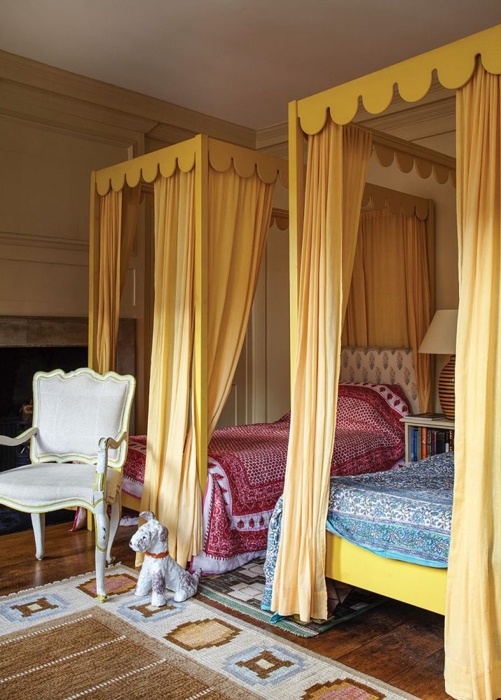 The room, as seen in 'Near & Far' by Lisa Fine, features two twin beds with scalloped-edged canopy frames painted yellow. Yellow fabric panels hang from the four corners of each canopy. One bed wears a blue and white patterned quilt; the other wears a red and white patterned quilt. A white French antique chair sits at the foot of one bed, next to a small dog statue. An area rug features subtle stripes in brown, framed by a natural-white border that displays geometric designs in soft blues and neutrals.