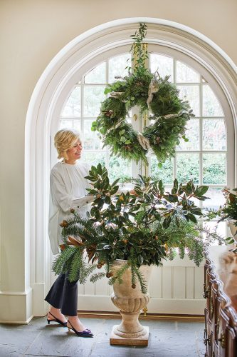 The designer stands in front of pair of large French double doors adorned with a large wreath. She is arranging branches of magnolia and yew.