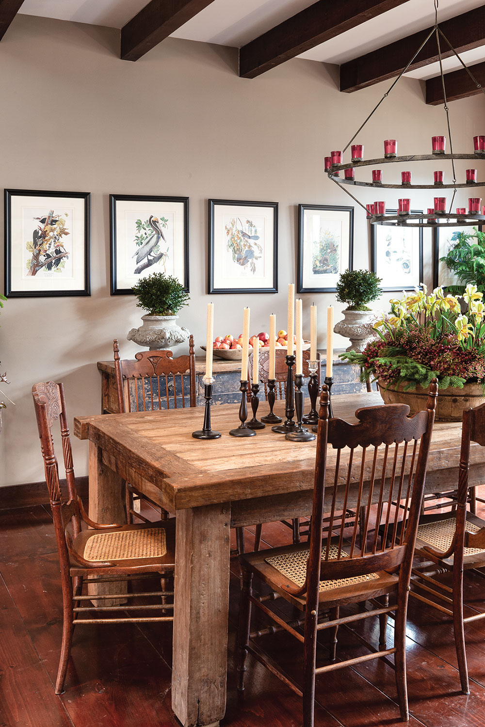 Dining room with exposed beams, a rustic heavy wood dining table, antique chairs, and a rustic-modern candle metal chandelier with red glass votives. Six Audubon prints are hung in a single row on the main wall.