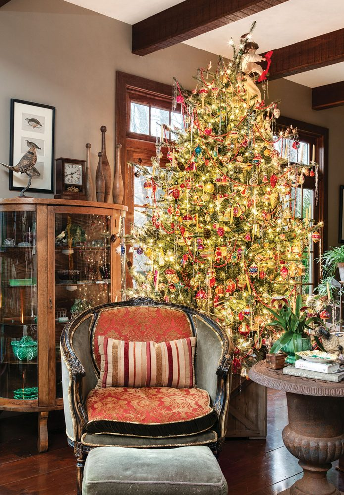 Living room vignette with an antique upholstered chair, antique wood and glass display cabinet, and a blue spruce covered in ornaments and white holiday lights