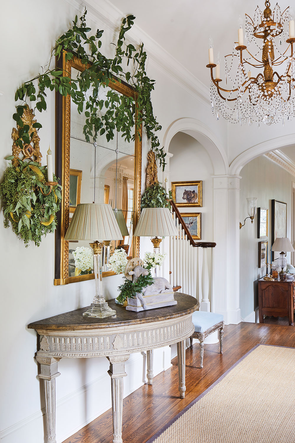 The painted foyer's architecture features high ceilings and gracious arches. Jane Schwab decorated it with a gilded chandelier adorned with delicate crystal swags, a simple sea grass or sisal rug, a semi-circle entry table, and a large gilded antique complemented by Italian sconces on either side.