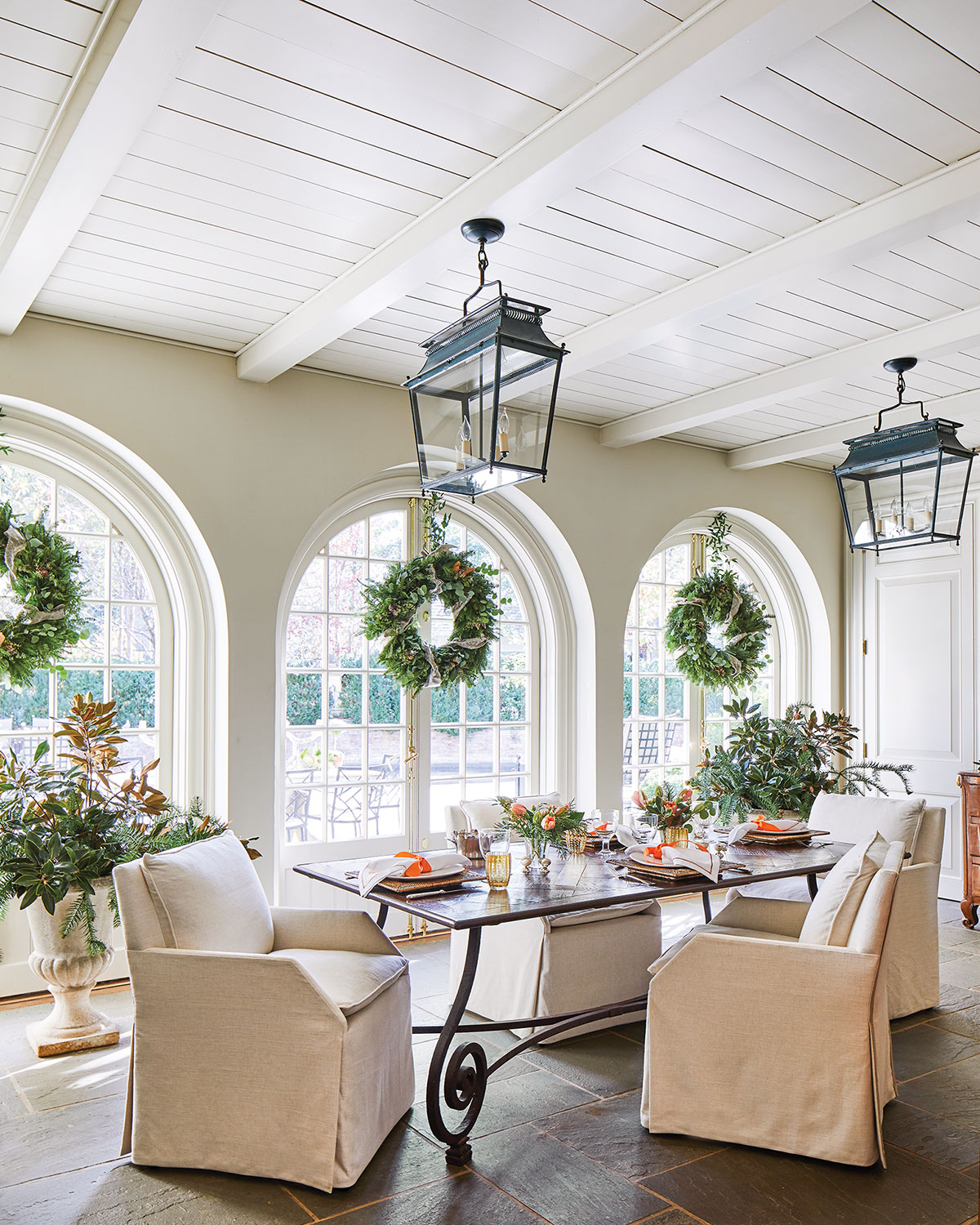 The light and airy garden room features a painted wood ceiling with exposed beams, three sets of arched French doors, and a natural wood dining table with a scrolled metal base, surrounded by natural linen slip-covered chairs. Two large black lanterns provide lighting.
