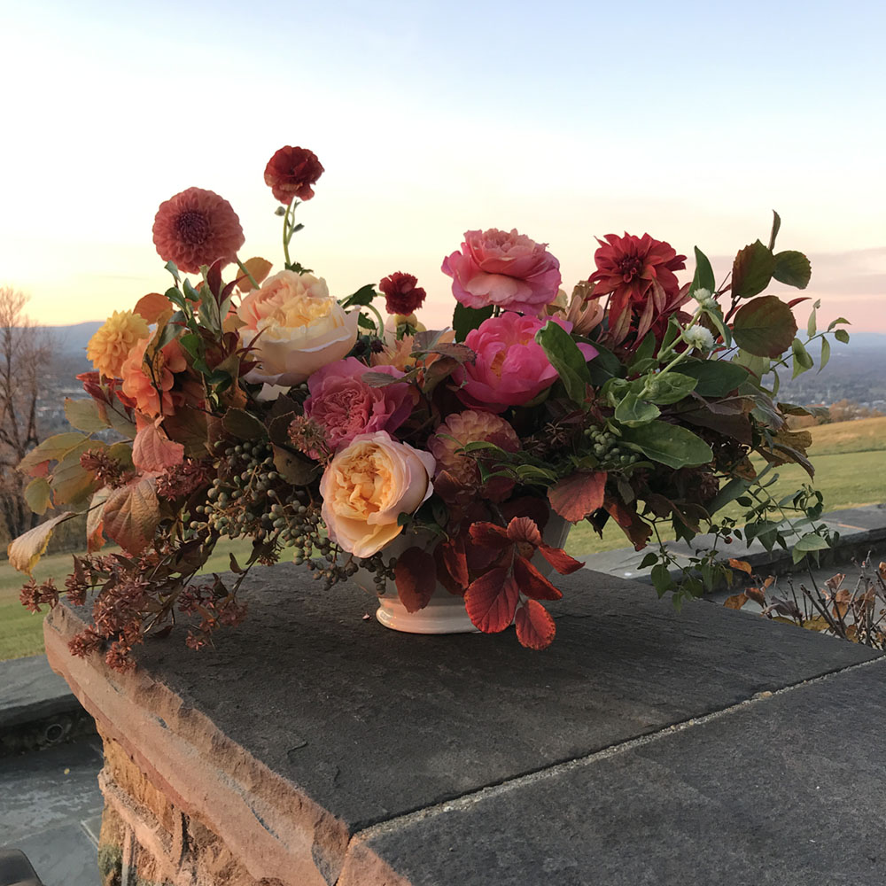 Flower arrangement set on a stone wall, with a scenic vista in the background.