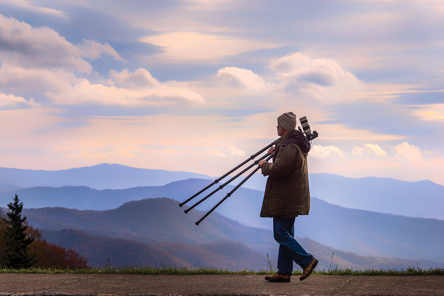 Sam Stapleton dressed in winter gear carries his tripod and camera as he walks along as sidewalk with a mountainous view in the background.