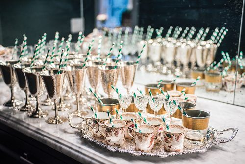 Green and white striped paper straws stand in silver goblets, stemmed crystal, and fine china mugs, which are lined up on a stone counter waiting to be filled with Brandy Freezes