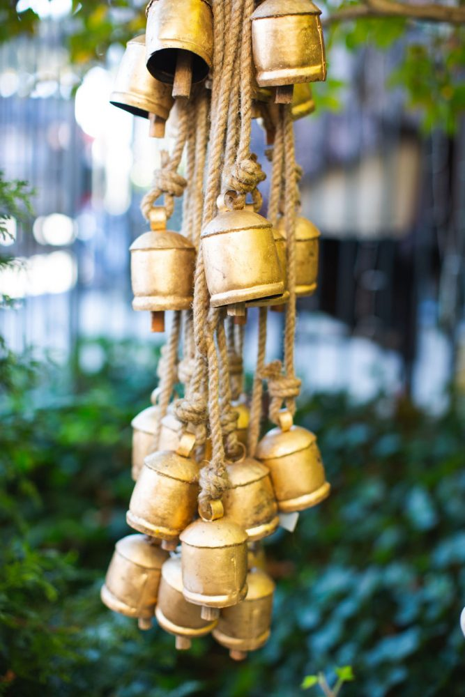 A bundle of antique holiday sleigh bells hanging from ropes