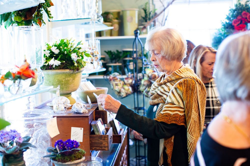 A guest at the open house peruses the gift selection at The Gardener's Cottage in Asheville, NC. Among the gifts are ample potted flowering plants and colorful blooms in vases.