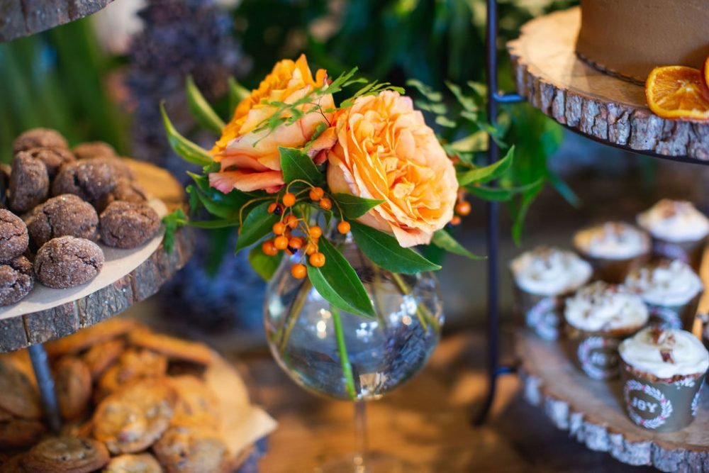 A small vase of apricot-colored roses, berries, delicate foliage sits among trays of assorted cookies and cupcakes at the holiday open house