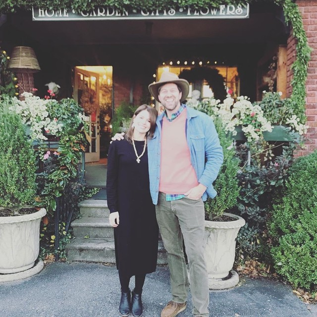 Libby Endry, wearing a long casual black dress and gold necklace, with James Farmer, dressed in chinos, a peach sweater over a plaid button, light blue jacket, and brimmed hat, stand in front of the Gardener's Cottage front porch, surrounded by a lush container garden