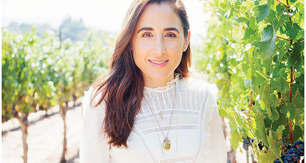 April Gargiulo, founder of Vintner's Daughter skin care, stands in a vineyard wearing a white 3/4-sleeve top and jeans