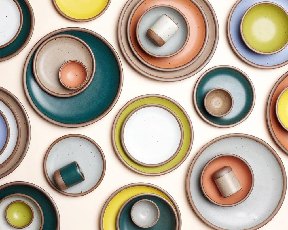 Best Shopping in Asheville, NC: A display of smooth glazed pottery plates by East Fork in a variety of muted, solid colors, such as peach, dark deal, gray, and white.