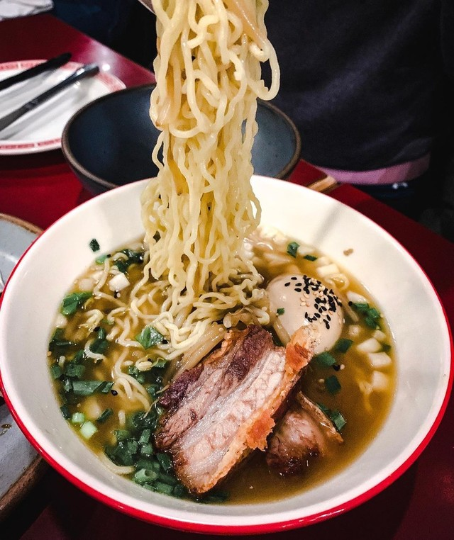 best ramen in Asheville: Chopsticks lift noodles from a brothy bowl of pork ramen at Gan Shan Station in Asheville