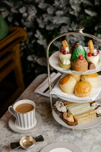 A tiered tray of sweets and savory finger sandwiches sits beside a cup of hot tea on a marble table at Dalloway Terrace in London