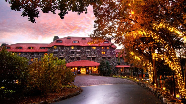 Best hotels in Asheville, NC: A view of the stone facade of The Grove Park Inn against a pink sunset. Twinkling tree lights follow the curve of the driveway, leading to the hotel entrance.