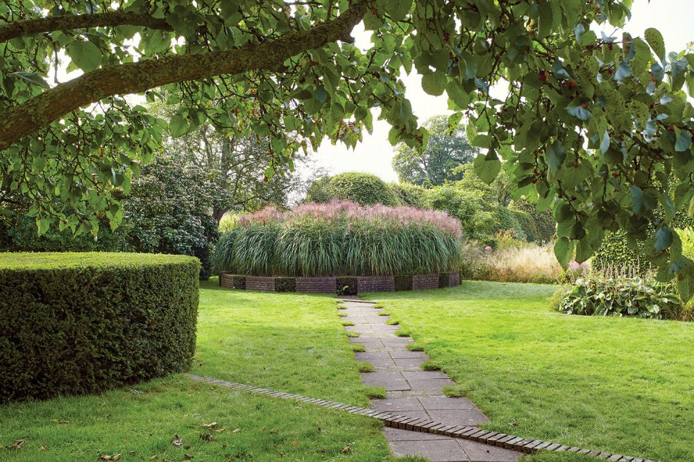 Piet Oudolf gardens; a circular trimmed hedge mirrors a circular planting of tall flowering grass