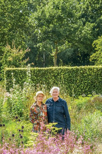 Portrait of the Dutch landscape designer (left), with silver hair and wearing a long sleeve denim buttonup, alongside his wife, wearing a colorful top and tan brimmed hat, in their private garden surrounded by grasses and perennial flowers
