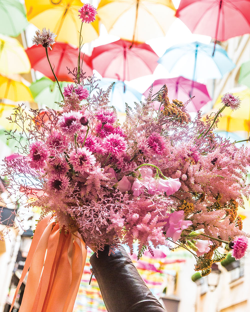 A hand holds lush pink bouquet tied with streaming peach ribbon against a colorful sky of suspended umbrellas