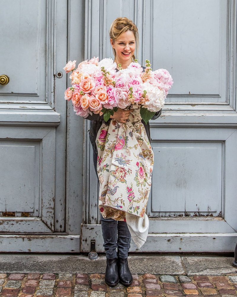 Parisian florist Catherine Muller stands on a brick-lined street in front of towering wooden double doors painted pale blue. She looks slightly away from camera and smiles, holding a profuse French bouquet of pink and white blooms, with the stems wrapped in a trailing floral fabric