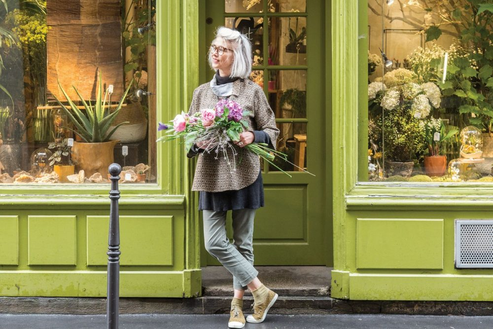 Parisian florist Clarisse Beraud stands casually in the doorway of her classic French storefront, with trim and a french door painted bright lime green.