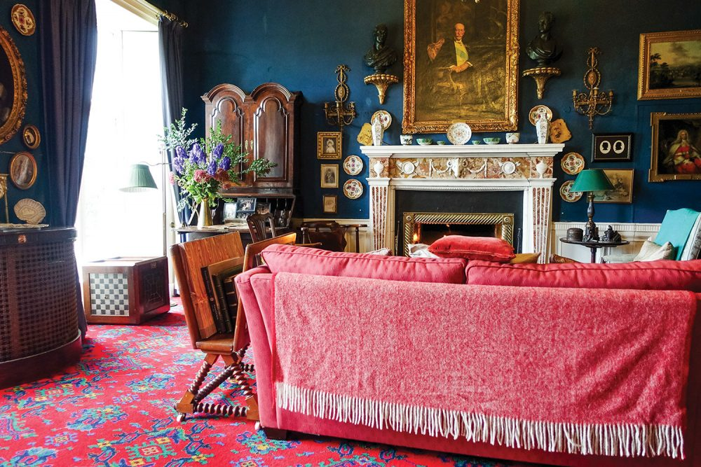 The library features dark blue walls and draperies; a plush, cherry red sofa with a matching fringed throw draped over the back, a bright red fine rug with a geometric pattern of bright teal, blue, and yellow; an ornate fireplace beneath a historical oil portrait in an elaborate gilt frame; and antique furniture and decor.
