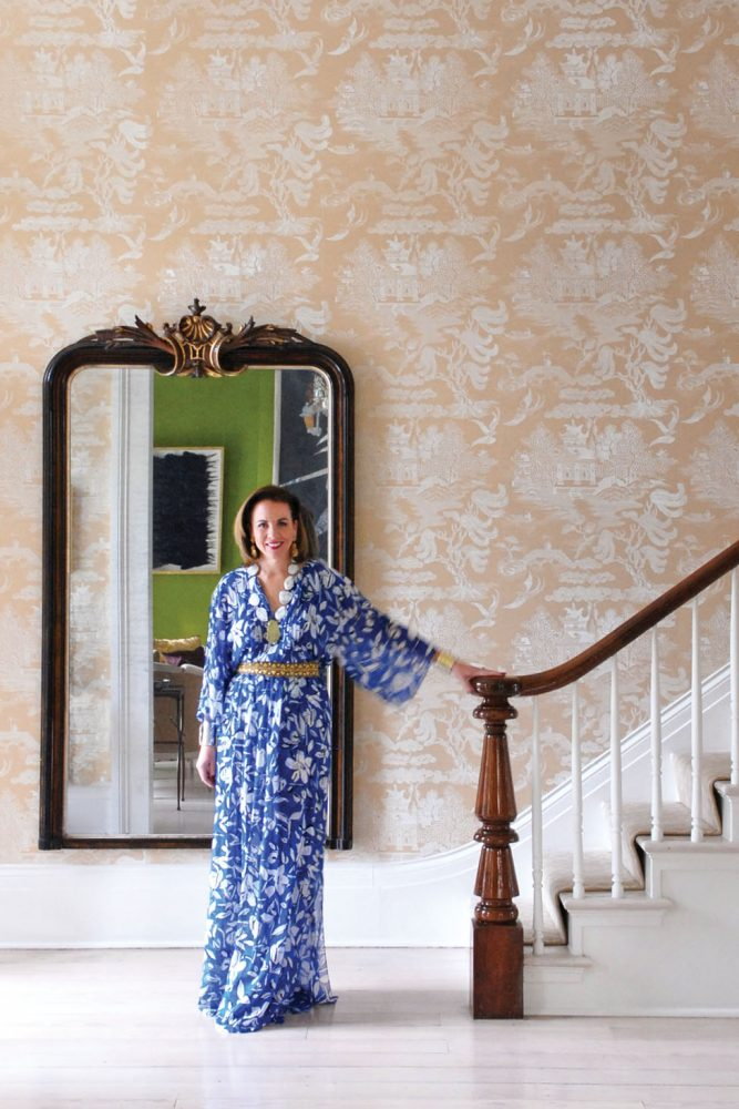 founder of Leontine Linens in a long, blue Oscar de la Renta dress with white flowers, stands at the bottom of an elegant staircase
