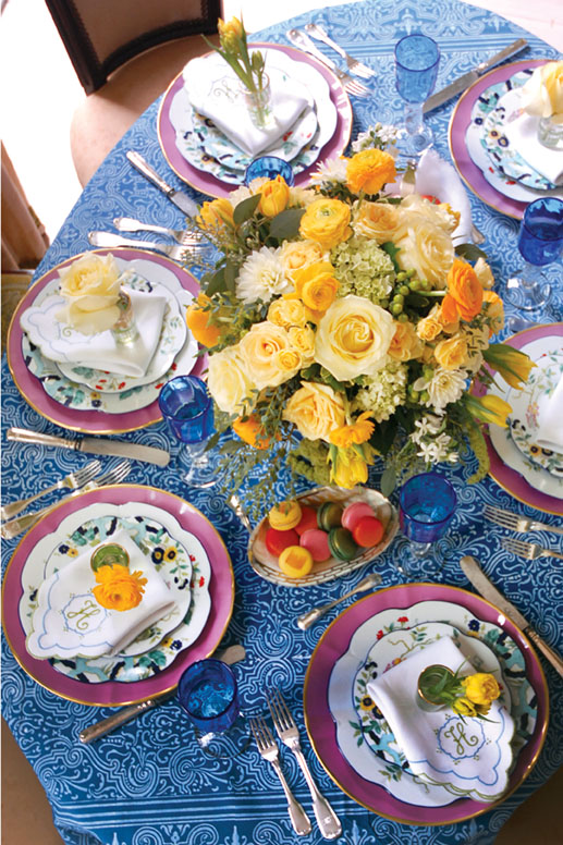 A cheerful table setting features a blue batik-print tablecloth, yellow flowers, pink chargers by Anna Weatherley, 'Paradis Bleu' plates by Royal Limoges, and scalloped white napkins with green and blue embroidery