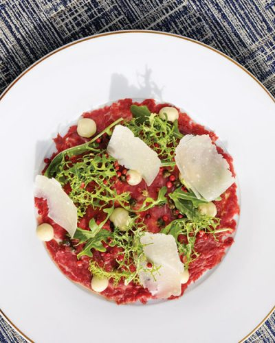 Carpaccio artfully plated in a white-brimmed white plate, garnished with fresh herbs and shaved cheese