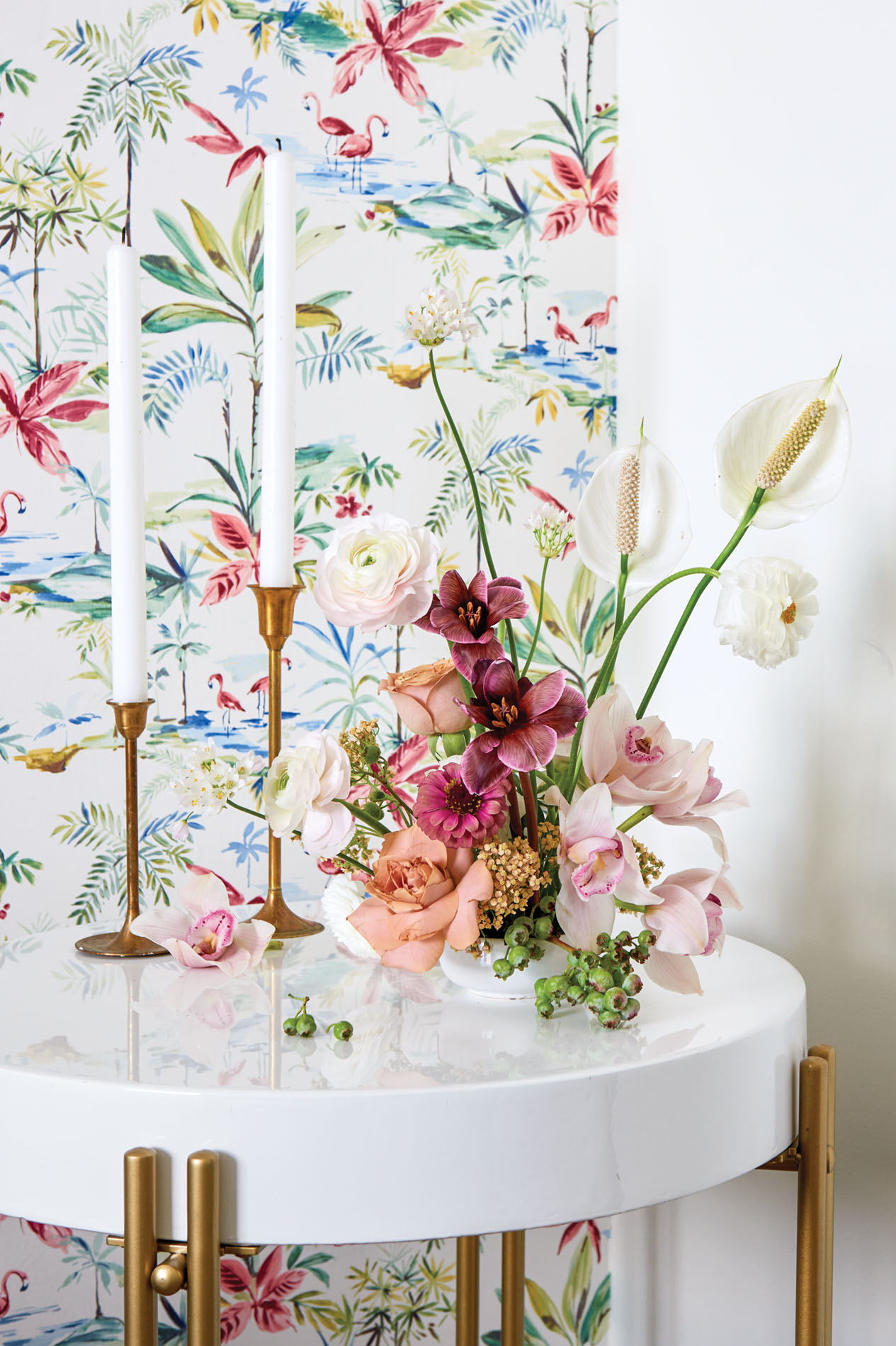 An ikebana arrangement and a pair of simple brass candlesticks with white tapers sit on a modern, white, circular occasional table with brass legs. A panel of floral fabric hangs in the background