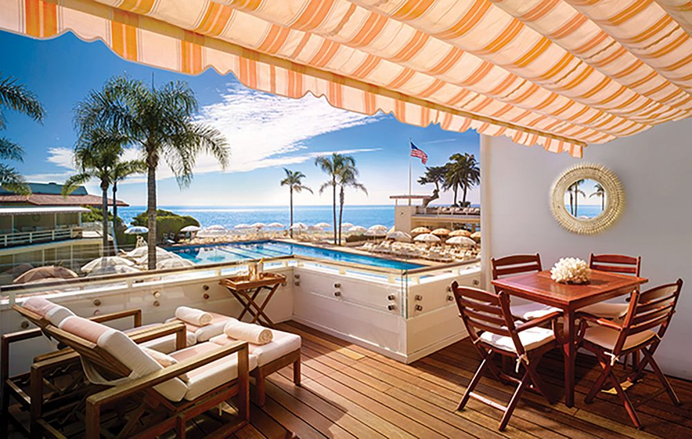 A covered patio area, featuring wood plant floors, teak patio furniture, and a yellow and white striped awning, looks out onto a pool at the Four Seasons Hotel Santa Barbara and a view of the coast beyond