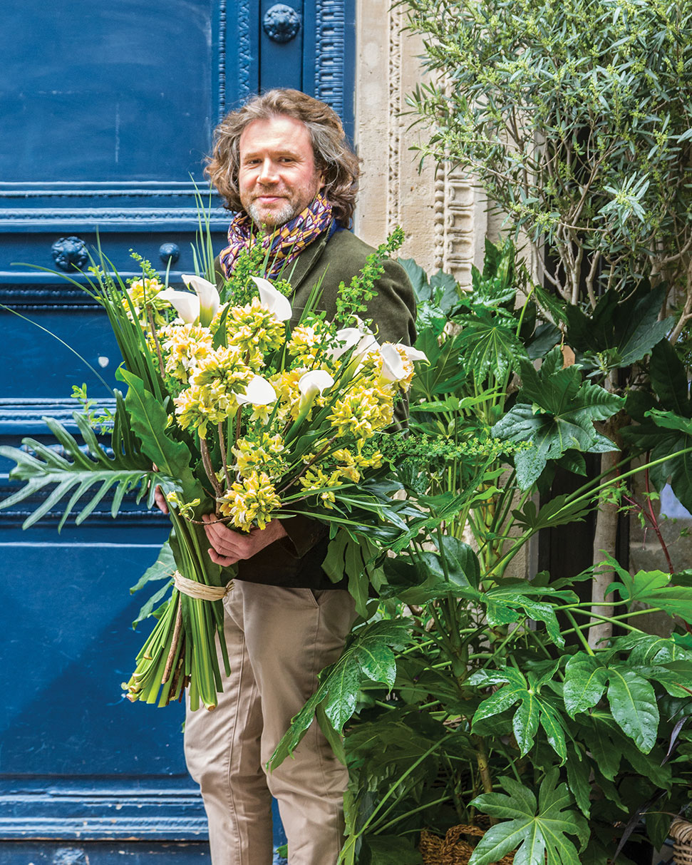 Parisian florist Stephane Chapelle stands against the bright blue painted door of this French flower shop, holding a massive bouquet of tropical yellow flowers and foliage.