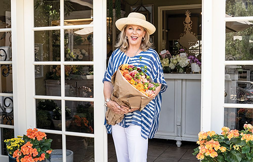 Designer Suzanne Tucker, dressed in a fashionable straw hat, a flowing blue and white strip top, white paints and sandels leaves one of her favorite flower shops in Santa Barbara, Hogue & Co., carrying a large bundle of flowers wrapped in papper