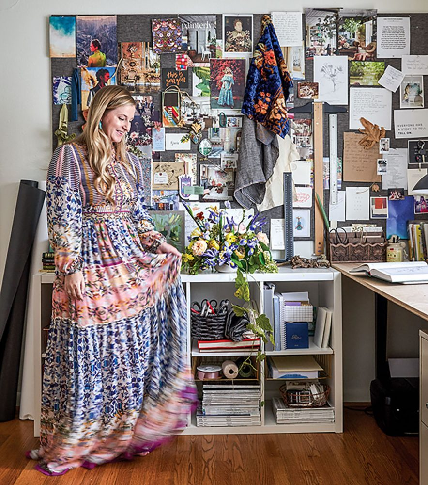 Artist Marcy Cook wearing a long Boho-style dress stands in front of her inspiration board in her studio