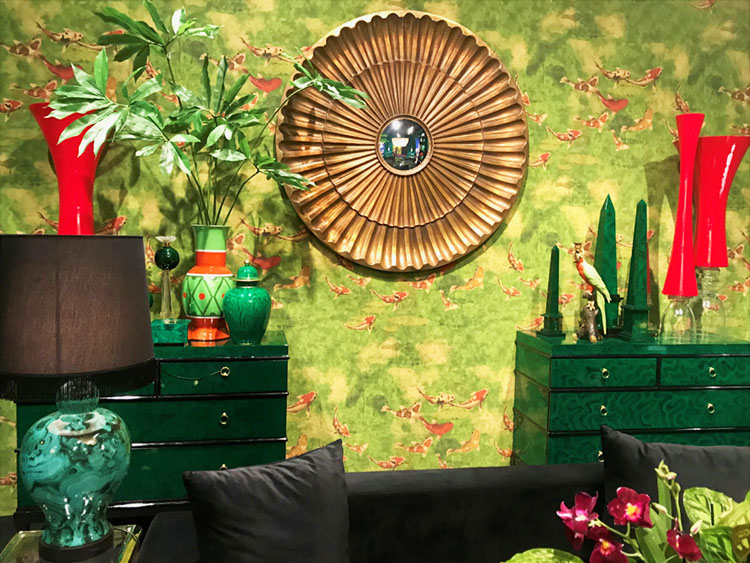 Scene from Maison & Objet 2020: A pair of deep green lacquered chest of drawers against a painterly green wall covering featuring orange fish. The space also features a marbled green glass lamp and red and green decorative objects