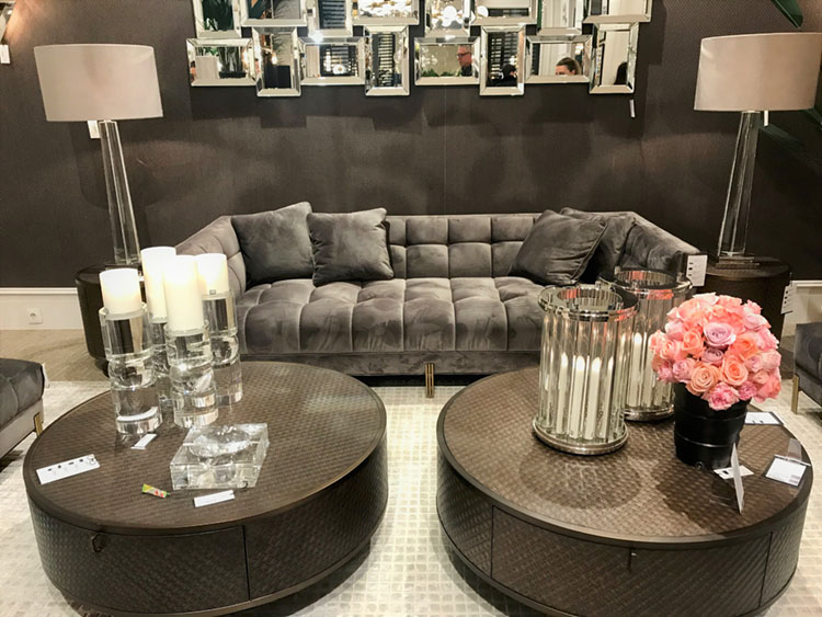 Scene from Maison & Objet 2020: A living room seating arrangement featuring a gray tufted soft, charcoal grey walls and two circular dark grey coffee tables toped with a vase of bright pink flowers. On the wall in the background is a modular display of mirrors