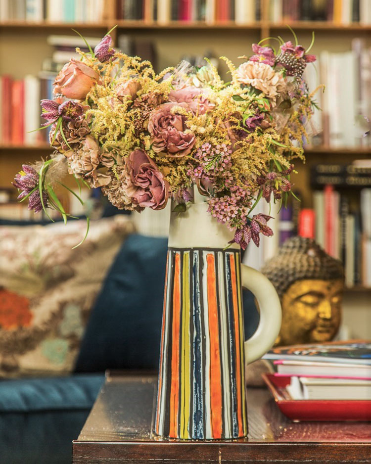 an arrangement of neutral and blush-toned blooms in a tall modern vase painted with vibrant vertical stripes in orange, green, yellow, and blue