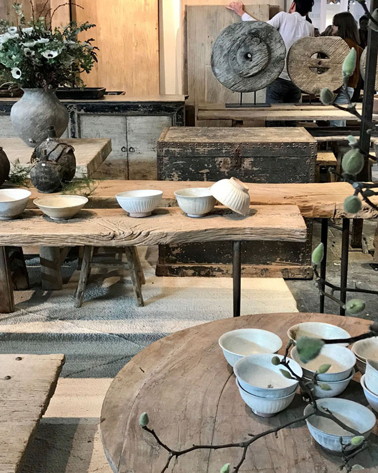 Scene from Maison & Objet 2020: natural, ash-toned wooden tables and benches, styled with white pottery