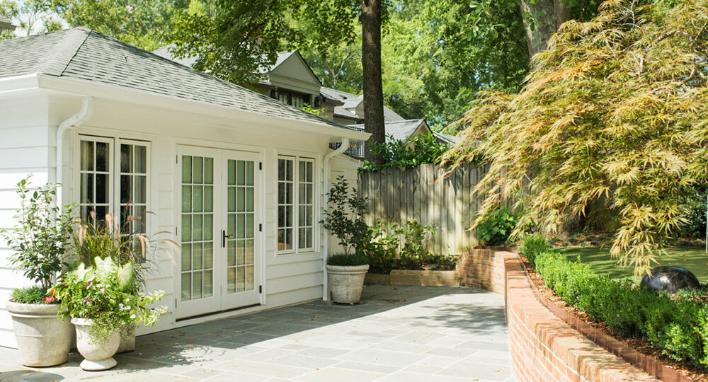 Paved entrance to a home accentuated with a container garden