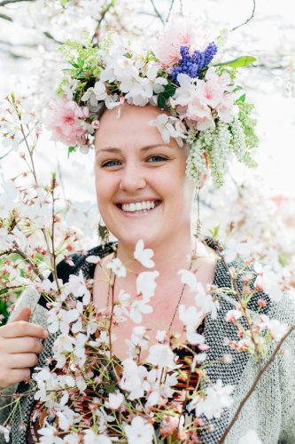 floral designer Natalie Ransom wears a lush crown of white, pink, and purple blooms, the fruits of spring flower foraging. She holds cut branches from a blooming cherry tree